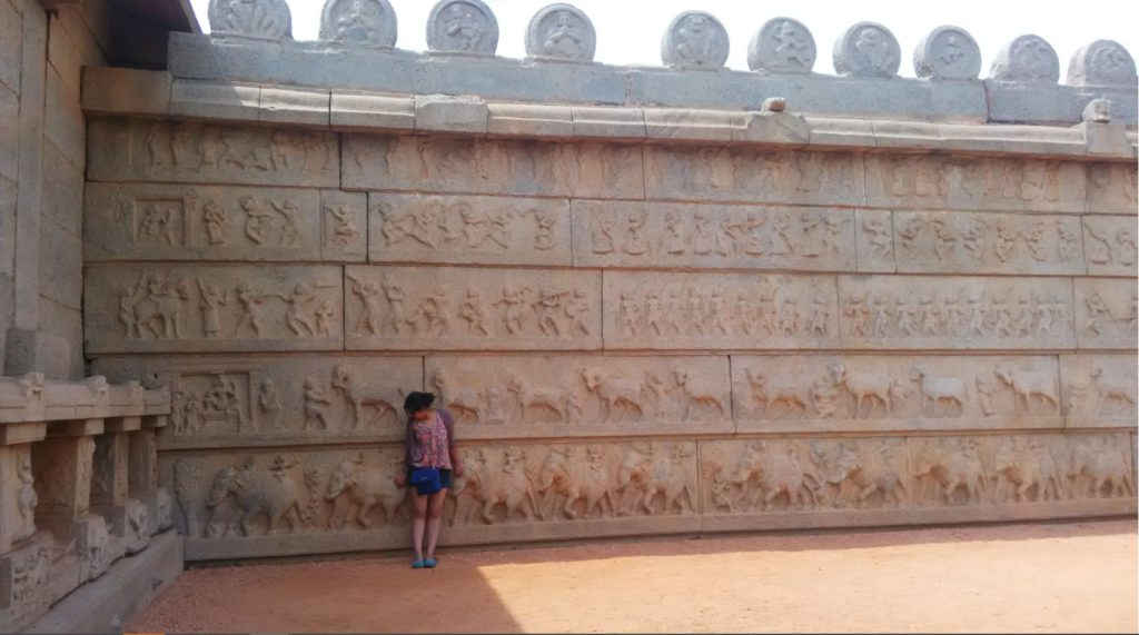 Stone wall with Dasara procession Hampi